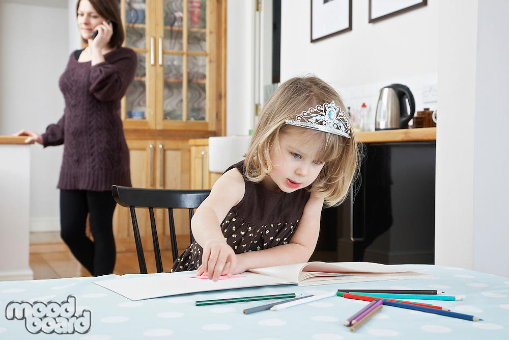 Girl (3-4) drawing mother on phone in background