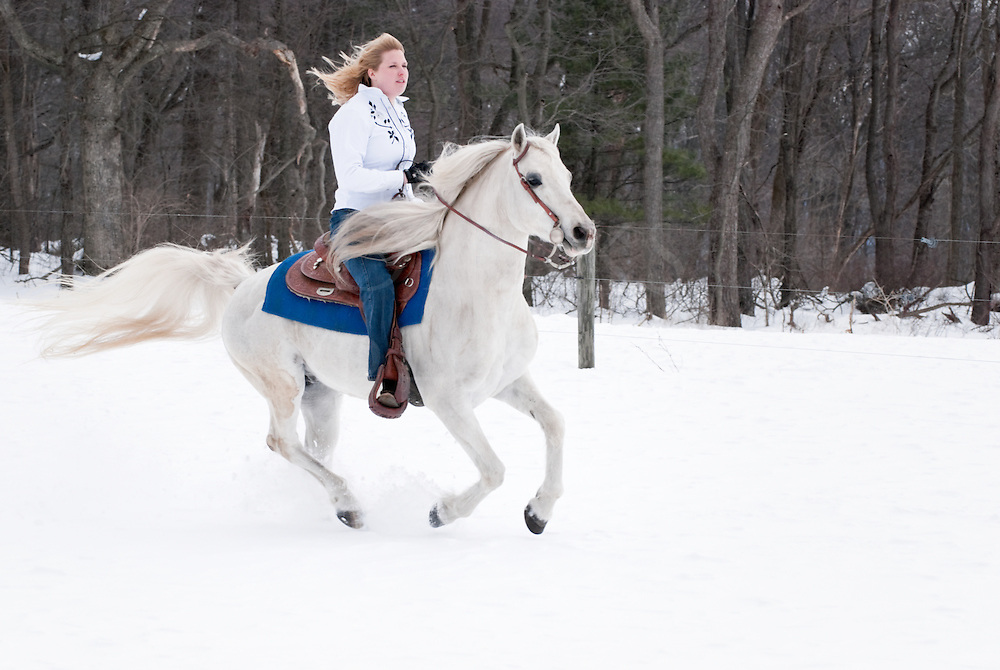 Picture of pretty blonde woman riding her white Arabian horse at the edge of a snowy woods.