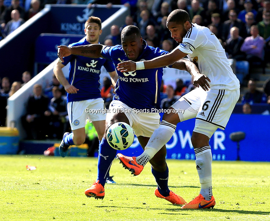 18th April 2015 - Barclays Premier League - Leicester City v Swansea - Ashley Williams of Swansea City battles for a ball with Jeff Schlupp of Leicester City - Photo: Paul Roberts / Offside.