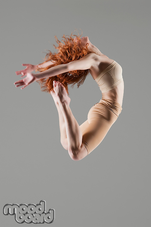 Dancer jumps with arms and legs bending nackwards