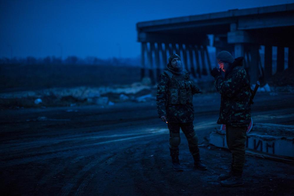 PERVOMAISKE, UKRAINE - NOVEMBER 19, 2014: Members of the Dnipro-1 brigade, a pro-Ukraine militia, keep watch at their base under a bridge as dusk settles in Pervomaiske, Ukraine. CREDIT: Brendan Hoffman for The New York Times
