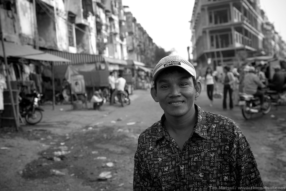 "Portrait of a moto taxi driver near a slum where the non governmental organization ""Acting for Women in Distressing Situations"" (AFESIP), conducts outreach and provides services in Phnom Penh, Cambodia. The permanent structure at left, a decaying four story building known simply as 'The Building', was built in the 1960's as transitional housing and now hosts a shantytown where many of the city's poor live, including many prostitutes, and is believed to have the highest rate of HIV infection in the city. AFESIP hands out free condoms, instructs prostitutes on HIV prevention, and conducts outreach in case the prostitutes need medical services, choose to leave their profession, or can report on cases of sex trafficking. AFESIP offers housing, education, training, and counseling for women who are victims of sex trafficking, worked as prostitutes, or are escaping domestic violence. Founded by Somaly Mam, who herself was once a prostitute and victim of trafficking and domestic abuse, AFESIP has three facilities in Cambodia and works with other NGO's to provide long term care for the women."