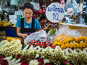 "11 AUGUST 2016 - BANGKOK, THAILAND:  A vendor makes flower garlands for use in Buddhist rituals in the flower section of Pak Khlong Talat in Bangkok. Pak Khlong Talat (literally ""the market at the mouth of the canal"") is the best known flower market in Thailand. It is the largest flower market in Bangkok. Most of the shop owners in the market sell wholesale to florist shops in Bangkok or to vendors who sell flower garlands, lotus buds and other floral supplies at the entrances to temples throughout Bangkok. There is also a fruit and produce market which specializes in fresh vegetables and fruit on the site. It is one of Bangkok's busiest markets and has become a popular tourist attraction.             PHOTO BY JACK KURTZ"