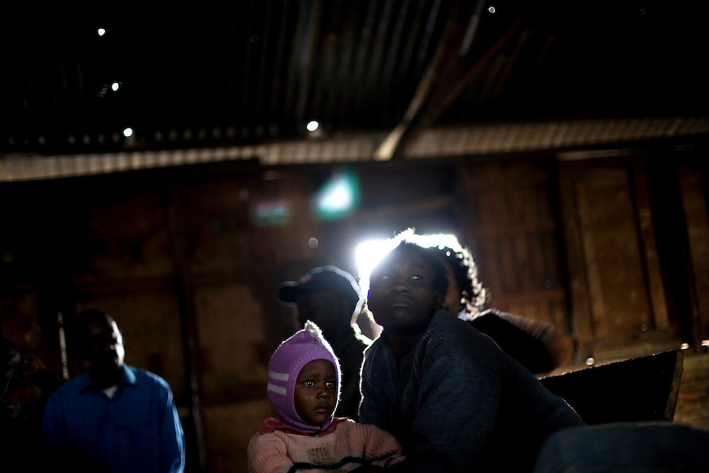 A mother and daughter sit in a community meeting in Mathare, one of the poorest slums in Nairobi.  Running water and electricity are scarce and trash and human waste fills the streets.  Many people have no jobs and those who do work can earn less than one dollar a day.