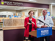 28 DECEMBER 2019 - URBANDALE, IOWA: US Senator ELIZABETH WARREN (D-MA), left, and pharmacist JOHN FORBES, owner of the Medicap Pharmacy in Urbandale, IA, talk about changes in law that will allow pharmacists to sell some hearing aids over the counter. Warren was at the pharmacy to announce that legislation she wrote will make hearing aids available over the counter. She said it should make hearing aids less expensive and increase competition in the hearing aid industry. The legislation was co-sponsored by Iowa Republican Senator Chuck Grassley and signed into law by President Trump. Warren is campaigning in Iowa this weekend to support her effort to be the Democratic nominee for the US presidential race in 2020. Iowa traditionally hosts the first presidential selection event of the campaign season. The Iowa caucuses are Feb. 3, 2020.           PHOTO BY JACK KURTZ