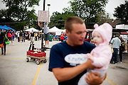 Nate Kirgis holds Parker Mary Ella Hart as a kid plays on a no parking sign at the Farmers' Market Saturday, Jun. 29, 2013, in Oak Park, Ill. Rob Hart/RobHartPhoto.com