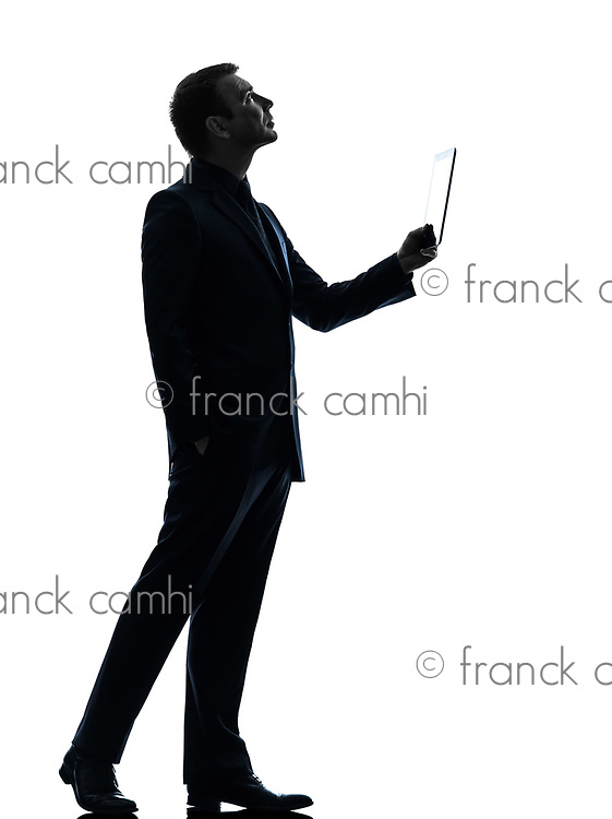 one  business man holding digital tablet looking up in silhouette on white background