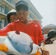 Older teenage boy on a moped with younger boy sitting behind him