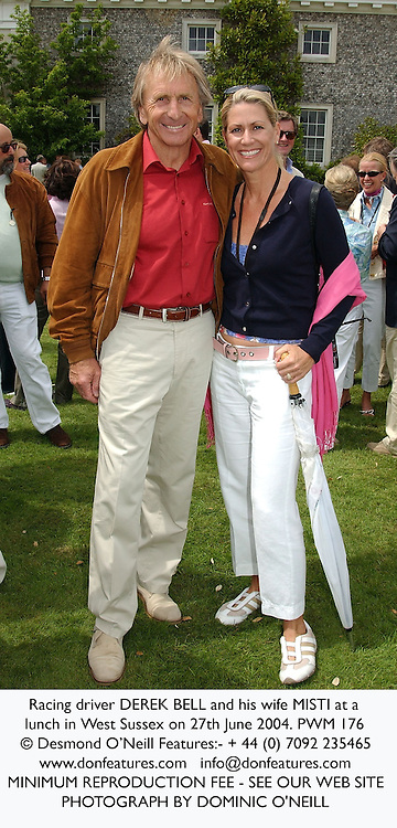 Racing driver DEREK BELL and his wife MISTI at a lunch in West Sussex on 27th June 2004.PWM 176