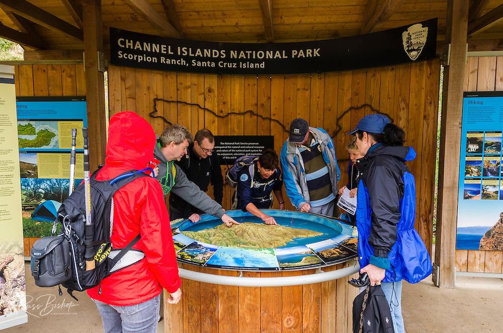 Visitors looking at interpretive display at Scorpion Ranch, Santa Cruz Island, Channel Islands National Park, California USA