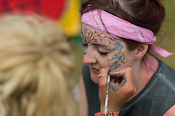 © Licensed to London News Pictures. 13/06/2014. Isle of Wight, UK.   A makeup artist applies festival makeup to a girls face at Isle of Wight Festival 2014.   The Isle of Wight festival is an annual music festival that takes place on the Isle of Wight. Photo credit : Richard Isaac/LNP