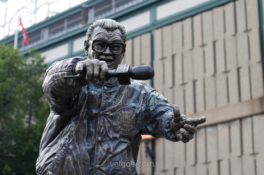 """Harry Caray statue outside Wrigley Field Chicago Cubs baseball park in Chicago, Illinois, USA. Born Harry Christopher Carabina March 1, 1914 he was a radio and TV broadcaster for Major League Baseball. He was nicknamed """"The Mayor of Rush Street"""" and was famous for singing Take Me Out to the Ballgame during the seventh inning stretch. High resolution prints and stock photos are availalble."""
