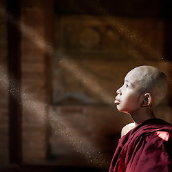 Young monk looking out the window. Sun rays showing the dust in the air, Bagan, Myanmar, Asia