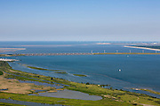 Nederland, Zuid-Holland, Haringvliet, 12-06-2009; Haringvlietsluizen en Haringvlietdam, gezien naar de tweede Maasvlakte. In de voorgrond natuurreservaat De Scheelhoek. De sluizen, onderdeel van de Deltawerken, zijn spuisluizen en zorgen er voor dat het zoete water uit het Haringvliet (rechts op de foto) zoals aangevoerd door Maas en Rijn geloosd kan worden. In het kader van modern natuurbeheer ('getemd getij') gaan de sluizen tegenwoordig bij eb én vloed beperkt open, om de getijden hun enigszin terug te laten komen in achterliggende estuarium .Dam and sluices between islands Voorne-Putten en Goeree-Overflakkee (bottom); the sluices are for draining water coming from the rivers Rhine and Maas (Meuse) from the natural bassin (right) to the North sea (left). Modern ecolical insight has led to opening the sluices semi-permanently, resulting in the estuary function of the Haringvliet patially being restored.Swart collectie, luchtfoto (25 procent toeslag); Swart Collection, aerial photo (additional fee required).foto Siebe Swart / photo Siebe Swart