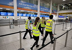 © Licensed to London News Pictures. 23/09/2019. Gatwick, UK. British Government officials wearing hi-vis vests walk past  closed Thomas Cook check-in desks at Gatwick Airport after the travel firm collapsed overnight. The 178 year old travel operator has gone in to liquidation after rescue talks failed overnight. This will trigger the largest peacetime repatriation as more than 150,000 British holidaymakers will need to be brought home. Photo credit: Peter Macdiarmid/LNP