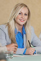 Portrait of young business woman at conference table