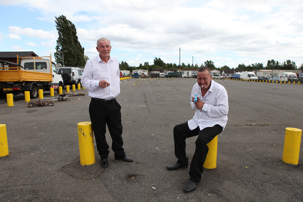 Irish Traveller men taking a cigarette break from a holy communion celebration on a site in West Drayton, near London.