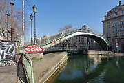 Passerelle Alibert, a steel footbridge built 1860 in the Marais basin, between the Quai de Valmy and the Quai de Jemmapes, on the Canal Saint-Martin in the 10th arrondissement of Paris, France. Behind is the rotating road bridge, the Pont tournant de la rue Dieu. The Canal Saint-Martin is a 4.6km long waterway between the Canal de l'Ourcq and river Seine, built 1802-25 to provide a fresh water source to the city and provide a trade route for canal barges. Picture by Manuel Cohen