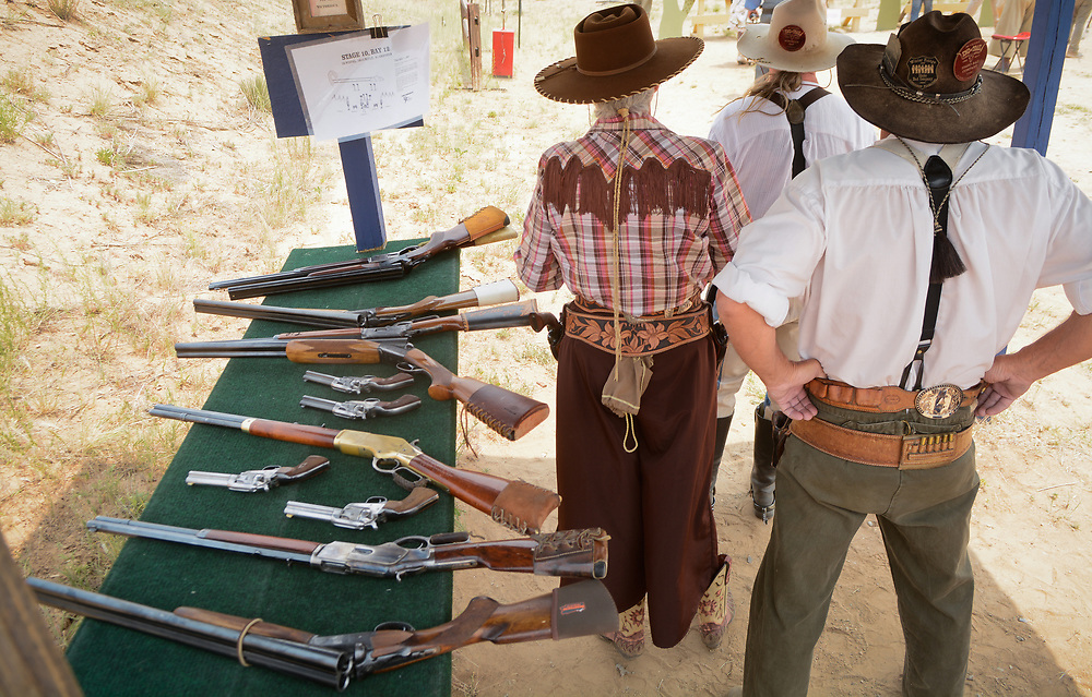 mkb062417h/metro/Marla Brose --  Alongside a table covered with firearms, Dale Canterbury, right, and Jennifer Yates, left, wait to compete in one of the stages in the 36th annual World Championship of Cowboy Action Shooting, Saturday, June 23, 2017, at Founders Ranch in Edgewood,  N.M. The public was welcome to watch on Friday and Saturday. The event ends on Sunday, a day which is closed to the public. (Marla Brose/Albuquerque Journal)