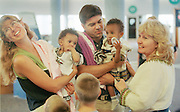 8/13/01 -- (PHOTO BY MIKE FENDER) w/ story, slug: AFRICA, file: 62040 // Cheryl Carter-Shotts, right, helps Amy and Paul Alford, from Bloomington, get adjusted with their new daughters Beza, left, and Bayush after arriving at the Indianapolis Airport.