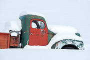 Old truck covered in snow, Wallowa Valley, Oregon.