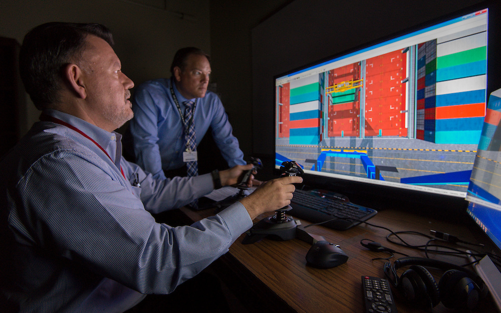 Yates High School instructor John Rydlund, left, practices on a shipping container crane simulator as Austin High School instructor John Buchanan, right, looks on during a training session at Austin, March 27, 2014.