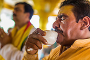 "09 SEPTEMBER 2013 - BANGKOK, THAILAND:  A Hindu priest blows a conch shell horn during Ganesha Chaturthi celebrations at Shiva Temple in Bangkok. Ganesha Chaturthi also known as Vinayaka Chaturthi, is the Hindu festival celebrated on the day of the re-birth of Lord Ganesha, the son of Shiva and Parvati. The festival, also known as Ganeshotsav (""Festival of Ganesha"") is observed in the Hindu calendar month of Bhaadrapada. The date usually falls between 19 August and 20 September. The festival lasts for 10 days, ending on Anant Chaturdashi. Ganesha is a widely worshipped Hindu deity and is revered by many Thai Buddhists. Ganesha is widely revered as the remover of obstacles, the patron of arts and sciences and the deva of intellect and wisdom.     PHOTO BY JACK KURTZ"
