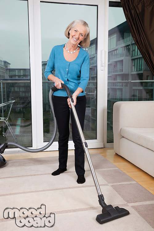 Portrait of happy senior woman cleaning rug with vacuum cleaner at home