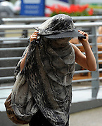 © Licensed to London News Pictures. 21/06/2012. Ascot, UK A woman hides from the rain. Ladies Day at Royal Ascot 21st June 2012. Royal Ascot has established itself as a national institution and the centrepiece of the British social calendar as well as being a stage for the best racehorses in the world.. Photo credit : Stephen Simpson/LNP