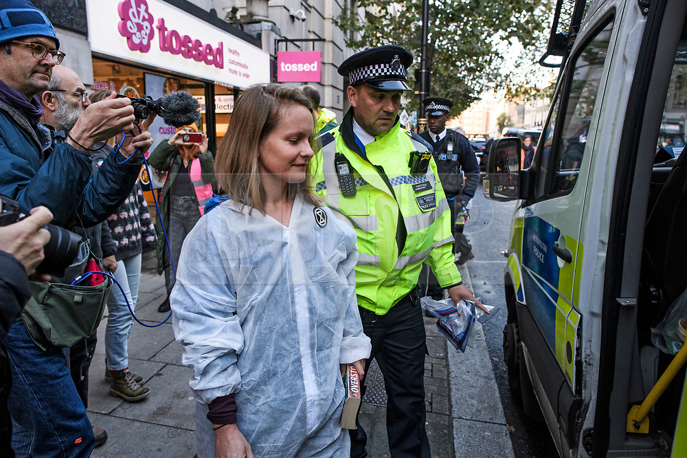 © Licensed to London News Pictures. 08/10/2019. London, UK. An Extinction Rebellion activist being arrested after glueing herself to the Department for Transport in Westminster. Activists have converged on Westminster for a second day, blockading roads in the area and calling on government departments to 'Tell the Truth' about what they are doing to tackle the Emergency. Photo credit: Ben Cawthra/LNP