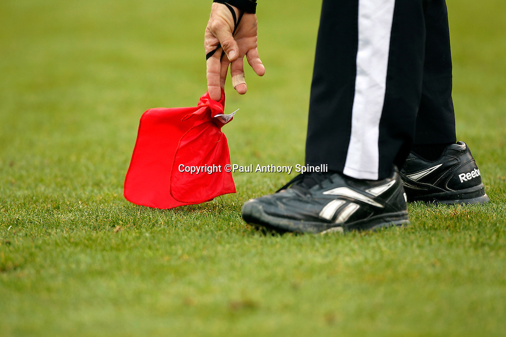 An NFL referee picks up a red challenge flag during the San Francisco 49ers NFL week 17 football game against the Arizona Cardinals on Sunday, January 2, 2011 in San Francisco, California. The 49ers won the game 38-7. (©Paul Anthony Spinelli)