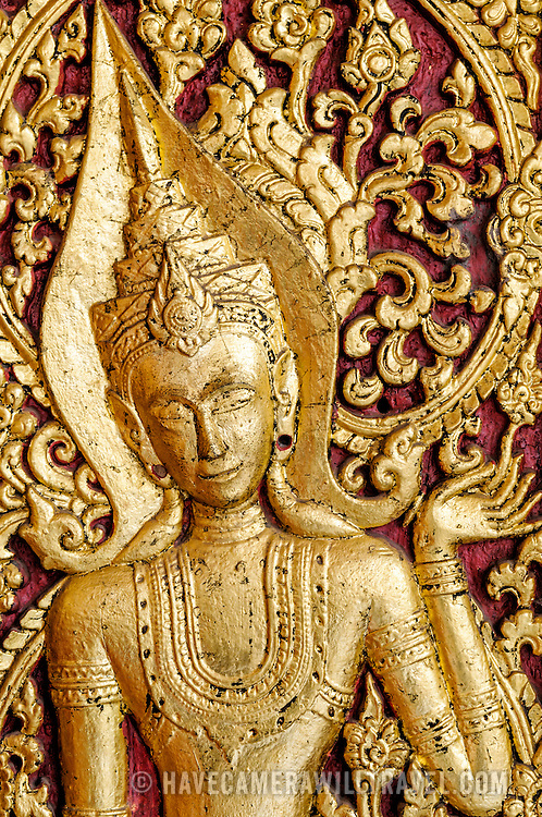 Gold and red decorations carved into the exterior wall at Wat Mai Suwannaphumaham.  Wat Mai, as it is often known, is a Buddhist temple in Luang Prabang, Laos, located near the Royal Palace Museum. It was built in the 18th century and is one of the most richly decorated Wats in Luang Prabang.