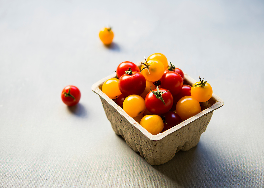 Red and Yellow cherry tomatoes in a pint basket stilllife