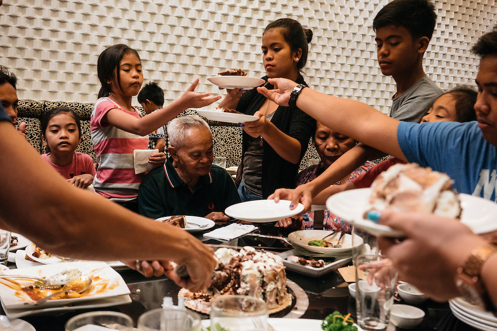 Teofilo Calda, center, celebrates his 82 birthday with his six children and 15 grandkids at Lugang Cafe at the Mall of Asia in Manila, Philippines.