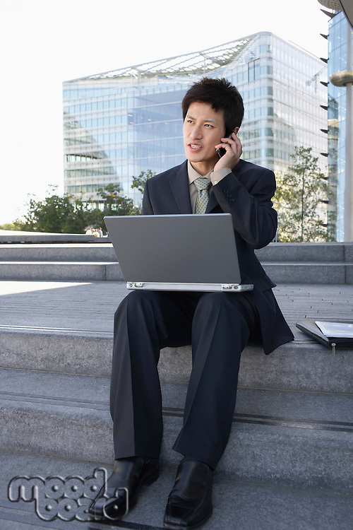 Businessman on outdoor Steps Using Laptop and talking on mobile