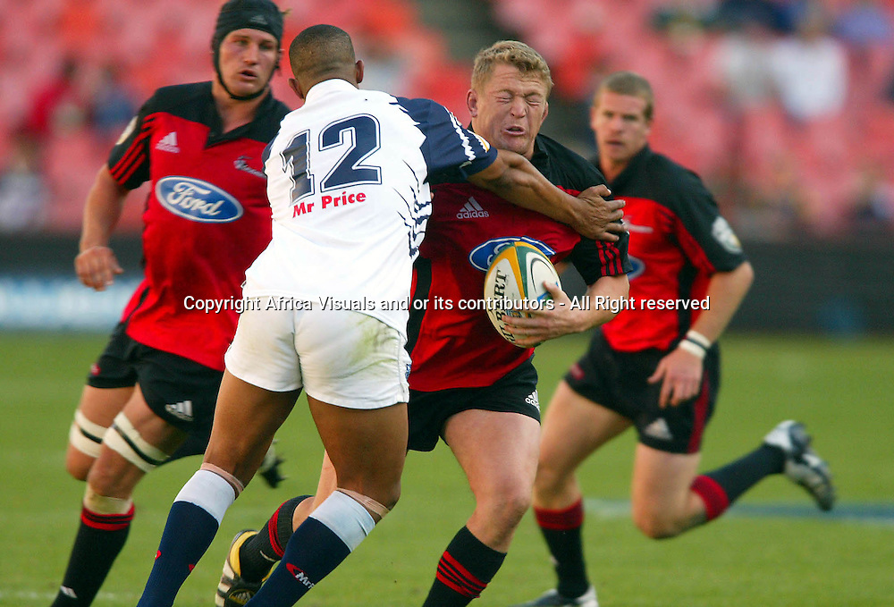 17 April, 2004. Rugby Union Super 12. Ellis Park, Johannesburg, South Africa. Cats vs Crusaders. Greg Somerville  runs into the tackle from Wayne Julies. The Crusaders won the match 39-37, with a last minute penalty conversion.<br /> Pic: Photosport