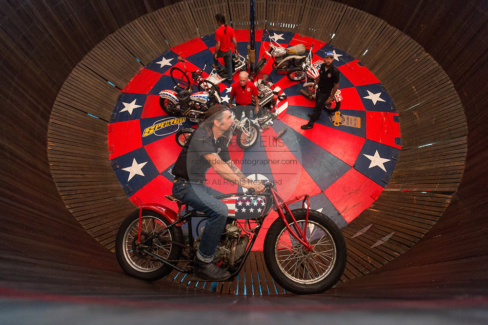 A motorcycle stunt performer rides along a vertical wall in the Wall of Death sideshow during the 74th Annual Daytona Bike Week March 8, 2015 in Daytona Beach, Florida. More than 500,000 bikers and spectators gather for the week long event, the largest motorcycle rally in America.