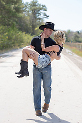 cowboy carrying a beautiful blonde girl on a dirt road