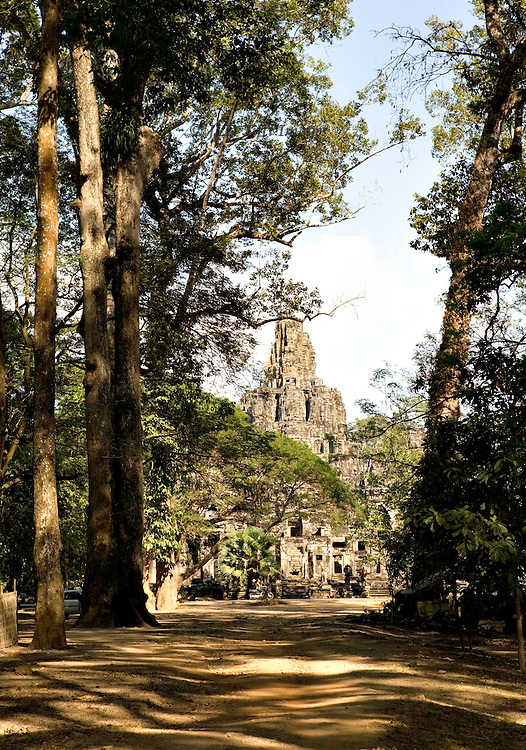 Distant towers of the Bayon (temple) seen from outside the west gate of Angkor Thom.  overhanging trees of the surrounding forest visible on either side in a picturesque aspect.