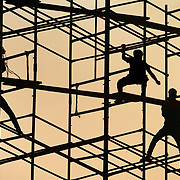City workers deconstruct scaffolding  at the Gateway of India  on the shore of the Arabian Sea in south Mumbai, India. The metal structure was used from festival from the weekend before.<br />