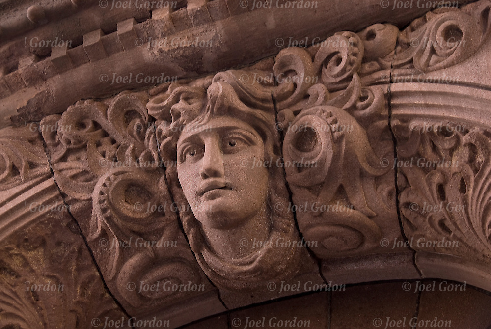 Architectural detail of face in stone, early 19th century artistic ornamental use on facade above outside door of building on East 12th Street in the East Village of New York City.