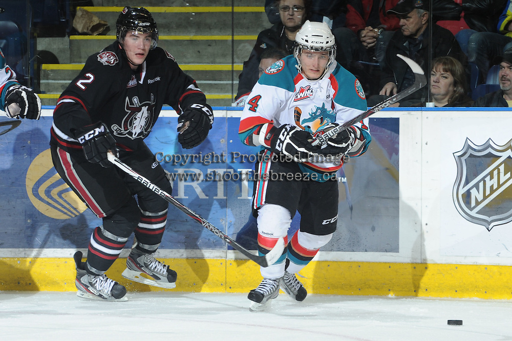 KELOWNA, CANADA - FEBRUARY 18: Devan Fafard #2 of the Red Deer Rebels checks Cody Chikie #14 of the Kelowna Rockets as the Red Deer Rebels visit the Kelowna Rockets on February 18, 2012 at Prospera Place in Kelowna, British Columbia, Canada (Photo by Marissa Baecker/Shoot the Breeze) *** Local Caption ***