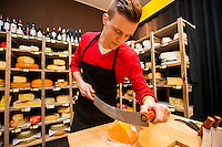 Male salesperson cutting cheese in store