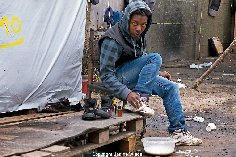 Young refugee from Sudan cleaning his shoes in The Calais Jungle Refugee and Migrant Camp in France