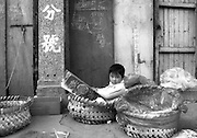 A girl plays in baskets at a produce market in an old Shanghai neighborhood, slated to be knocked down to make way for modern buildings and shops.