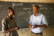 Calvin Doe (right), Youth Ambassador for The Kraft Cocoa Partnership talking to Daniel one of the teachers at the Mbaem community school n the eastern region of Ghana.
