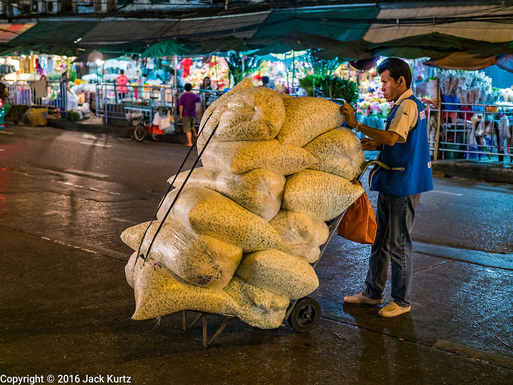 24 FEBRUARY 2016 - BANGKOK, THAILAND:  A porter delivers buds used to make flower garlands to a vendor before dawn at Pak Khlong Talat. Bangkok government officials announced this week that vendors in Pak Khlong Talat, Bangkok's well known flower market, don't have to move out on February 28. City officials are trying to clear Bangkok's congested sidewalks and they've cracked down on sidewalk vendors. Several popular sidewalk markets have been closed in recent months and the sidewalk vendors at the flower market had been told they would be evicted at the end of the month but after meeting with vendors and other stake holders city officials relented and said vendors could remain but under stricter guidelines regarding sales hours. The flower market is one of the best known markets in Bangkok and has become a popular tourist destination.       PHOTO BY JACK KURTZ