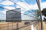 Europa, Deutschland, Koeln, Rheinbruecke der Autobahn A1 zwischen Koeln und Leverkusen. Blick durch die glaeserne Schallschutzwand auf ein Schild mit dem Hinweis, dass an der Bruecke gearbeitet wird. Wegen massiver Schaeden ist die Bruecke für Fahrzeuge ab 3,5 t gesperrt und es gibt ein Tempolimit. - <br /> <br /> Europe, Germany, Cologne, the Rhine bridge of the Autobahn A1 between Cologne and Leverkusen. Looking through the glass noise barrier on a sign that informs about repair work. Due to massive damages the bridge is barred for vehicles over 3,5 tons and there is a speed limit.
