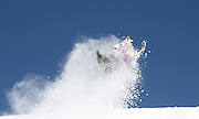 Tim Hoff riding his Skidoo into the sky with an explosion of powder snow enveloping him in the air