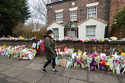 © Licensed to London News Pictures. 28/03/2018. Liverpool, UK. A woman walks past rows of flowers and tributes left outside Ken Dodd's lifetime home in Knotty Ash on the morning of the funeral of comedian and performer Sir Ken Dodd , who died on 11th March 2018 at the age of 90 . Photo credit: Joel Goodman/LNP